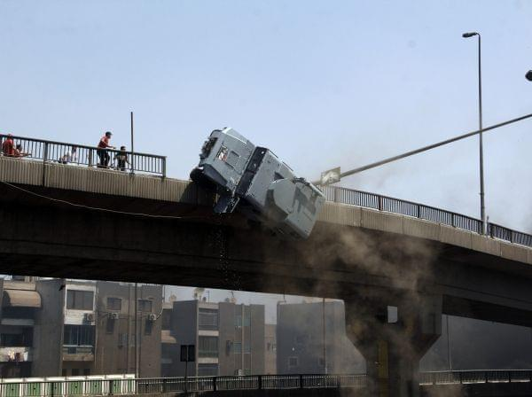 A police vehicle is pushed off of the 6th of October bridge by protesters close to the largest sit-in by supporters of ousted Islamist President Mohammed Morsi in the eastern Nasr City district of Cairo, Egypt, Wednesday, Aug. 14, 2013.