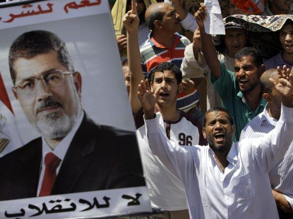 Supporters of Egypt's ousted President Mohammed Morsi shout slogans under his poster following Friday prayers in Nahda square, where protesters installed their camp near Cairo University in Giza, southwest of Cairo, Egypt, Friday, Aug. 9, 2013. Protesters demand Morsi's reinstatement, restoration of the suspended constitution drafted under Morsi and the return of his Islamist-dominated legislative council which was also disbanded. The Arabic on the poster reads,