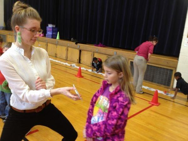 Liesel Booth, a teacher's aide at Wiley Elementary School in Urbana, shows a card  to first grade student, Cassie Wefel. Wefel must then put on a red foam glove, and hit a picture on a wall that matches the word.