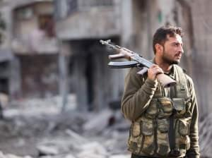 A Free Syrian Army fighter holds his rifle as he stands on a damaged street in Aleppo on Nov. 29, 2012.