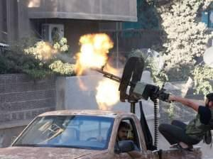 A member of the Free Syrian Army opens fire with a machine gun during clashes with Syrian army forces in Aleppo on Sept. 27, 2012.
