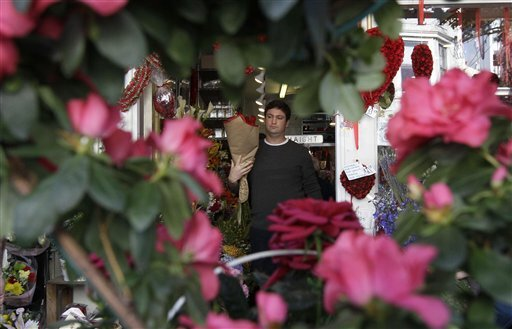 Mark Dorshkind carries roses he bought for Valentine's Day at Flowers of the Valley in San Francisco, Tuesday, Feb. 14, 2012.