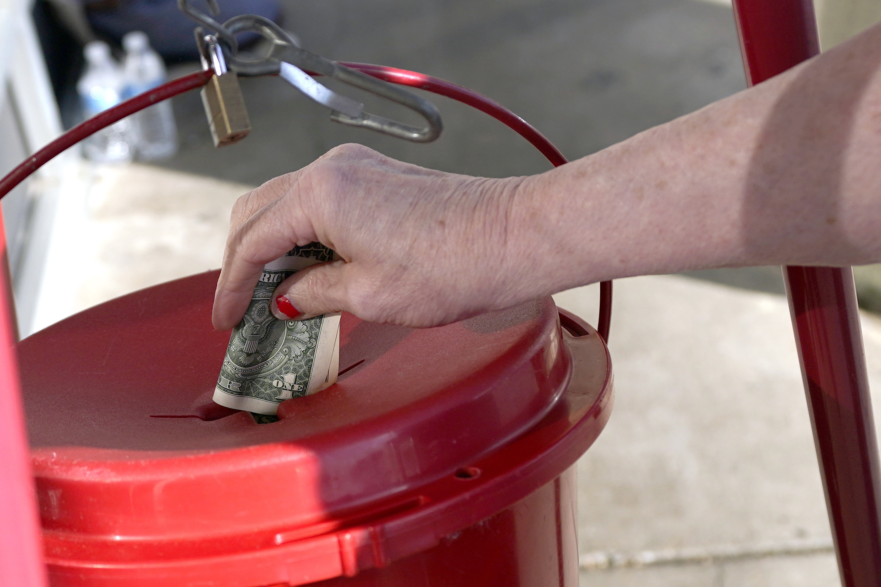 """A Corner Market grocery store customer places a dollar in the iconic Salvation Army collection bucket in Jackson, Miss., Wednesday, Nov. 25, 2020, as a bell ringer, unseen, wishes customers a """"Happy Thanksgiving."""""""