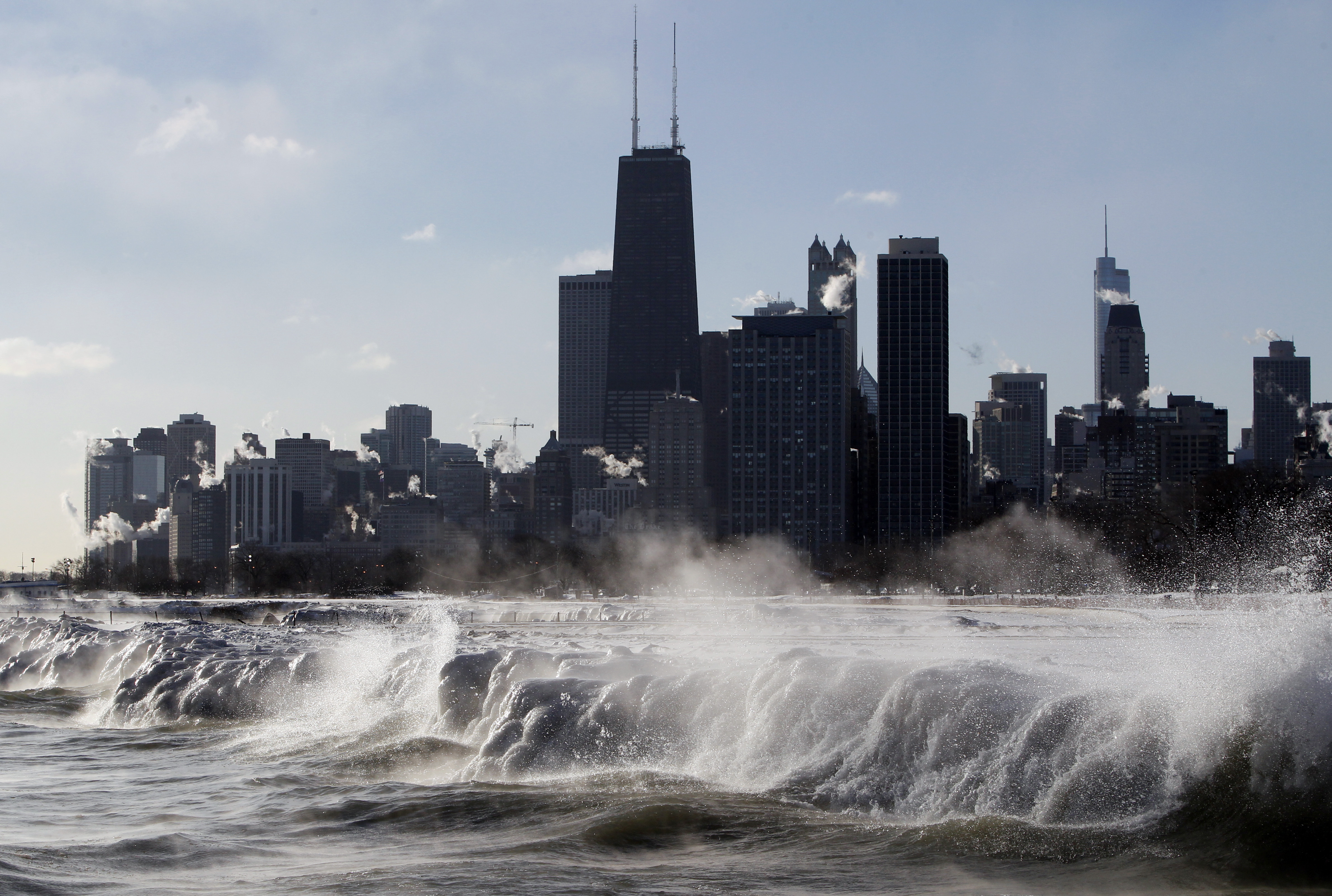 Jan. 27, 2014, file photo, ice forms as waves crash along the Lake Michigan shore in Chicago.