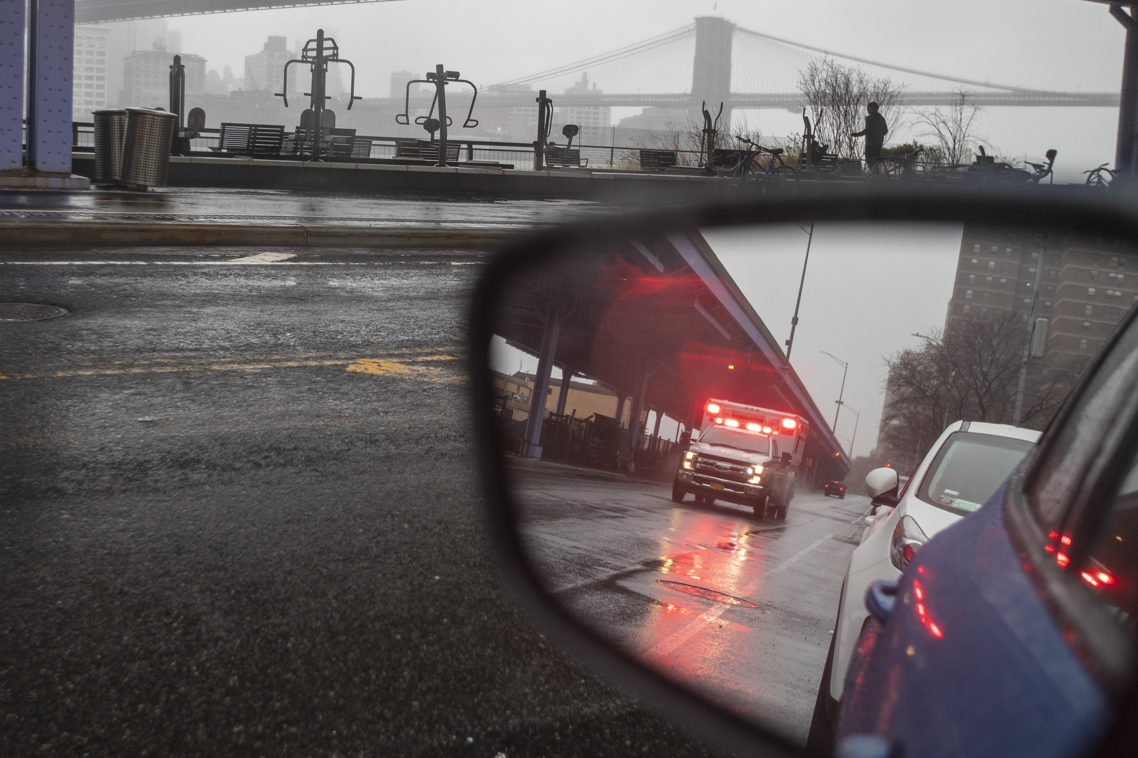 An ambulance is seen with it's emergency lights on in lower Manhattan, Sunday, March 29, 2020. The new coronavirus causes mild or moderate symptoms for most people, but for some, especially older adults and people with existing health problems, it can cause more severe illness or death.