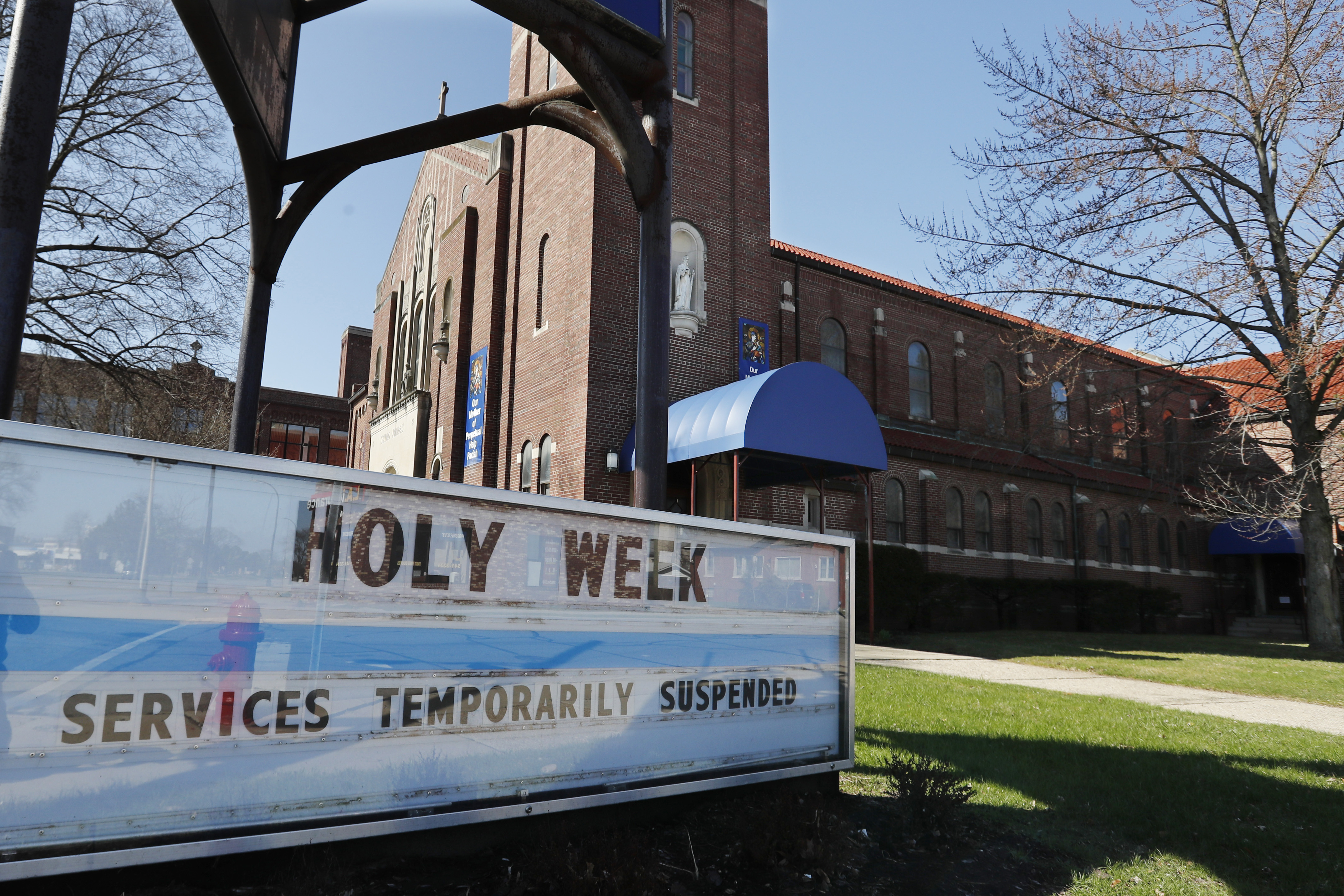 A sign highlighting Holy Week activities is displayed outside the Our Mother of Perpetual Help- St. James Parish, Wednesday, April 8, 2020, in Ferndale, Mich. Church activities during Holy Week are being suspended across the state and the world as the coronavirus pandemic continues spreading.