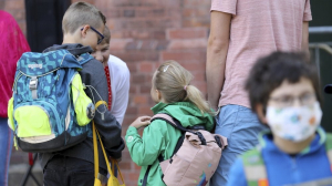 Students are brought to school by their parents in Rostock, Germany Monday, Aug. 3, 2020 as Mecklenburg-Western Pomerania is the first federal state to resume regular school operations throughout the state. About 150,000 students are expected to attend their schools.