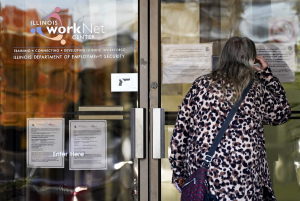 A woman checks information as information signs are displayed at IDES (Illinois Department of Employment Security) WorkNet center in Arlington Heights, Ill., Thursday, Nov. 5, 2020. Illinois reports biggest spike in unemployment claims of all states.