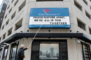 Un hombre ajusta el rótulo de One America en el centro de Indianapolis. Usualmente enseña una broma, pero el mensaje antes del mensaje de Gobernador dice: