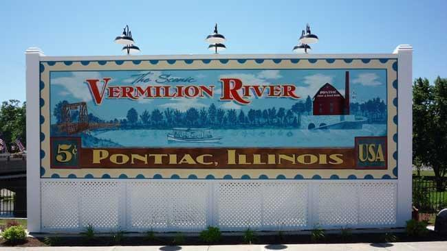 Painted sign in the shape of a postage stamp saying Vermilion River