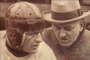 Red Grange talking with a football coach