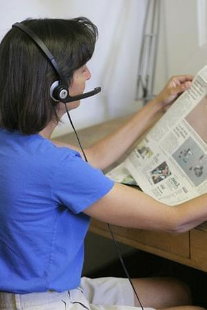 an Illinois Radio Reader volunteer reading a newspaper into a microphone