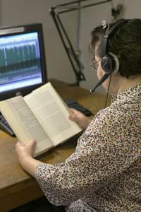 an Illinois Radio Reader volunteer reading a book into a microphone