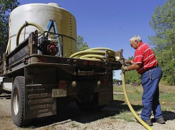 Carl Marion of Athens, Ill., pumps water from his 2,000 gallon water tank