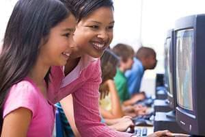 Teacher and student smiling as they look at a computer