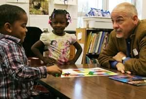Book mentor Joe Murphy plays an educational dinosaur game with children.