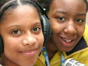 two students sitting in front of radio microphone