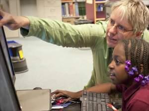 Kimberlie Kranich helping student edit video at computer.