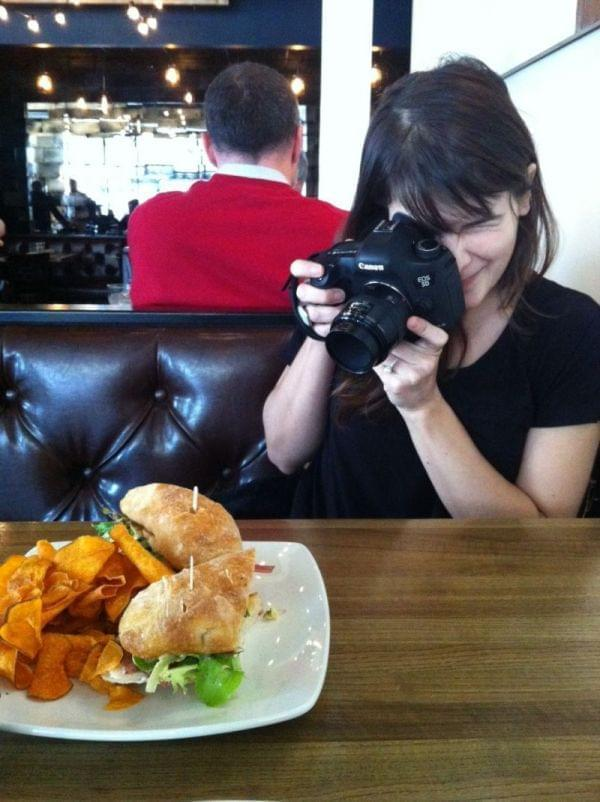 A young woman taking a photo of food at a restaurant.