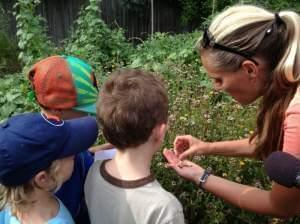 Woman showing a group of small children seeds in her hand.