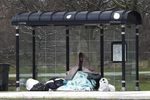 A homeless man occupies a Chicago Transit Authority bus shelter during the coronavirus pandemic on the city's West Side Wednesday, April 15, 2020.