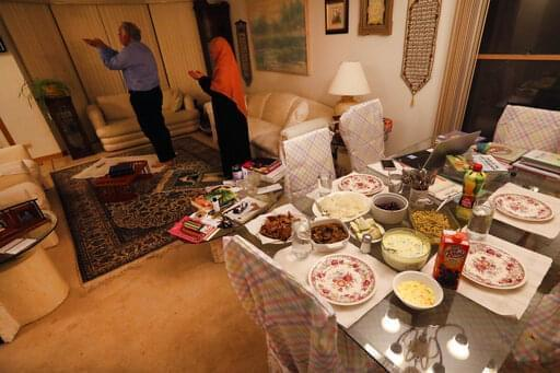 In this photo from April 28, 2020, Asghar Ali Khan and his wife, Shaheen, participate in the evening prayer as the Iftar, the evening meal with which Muslims end their daily Ramadan fast at sunset, waits on the dining room table at their Wheeling home.