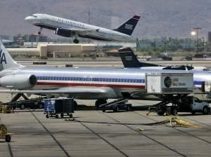 US Airways jet takes off as an American Airlines jet is prepped for takeoff