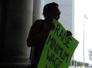 Wendy Brown holds sign before an Occupy Albany rally pushing for a raise in New York's minimum wage