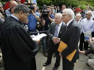 Cook County Chief Judge Tim Evans, left, presides over the civil union of James Darby, center, and Patrick Bova during ceremonies in Chicago's Millennium Park Thursday, June 2, 2011 in Chicago.