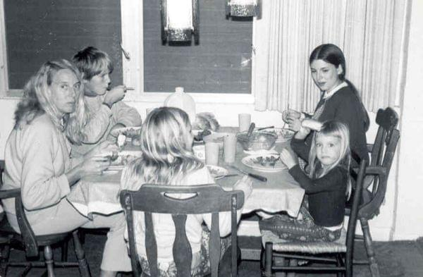 A young girl and several family members having dinner around the table.