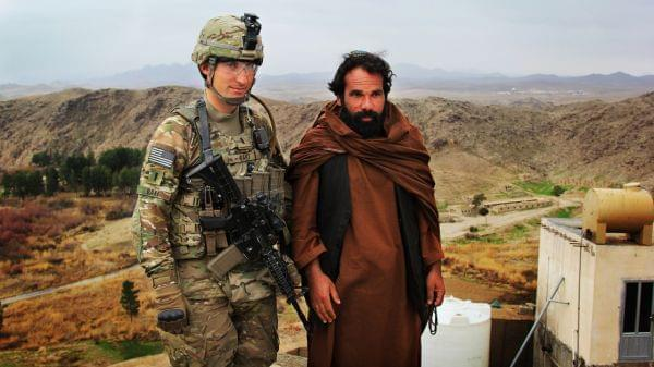 Marine Lt. Phillip Baki visits with an Afghan police officer, Abdul Karim