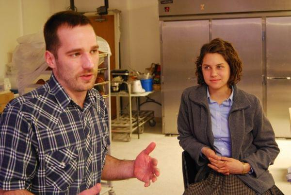 A young man and woman in a baking facility, sitting on stools, talking