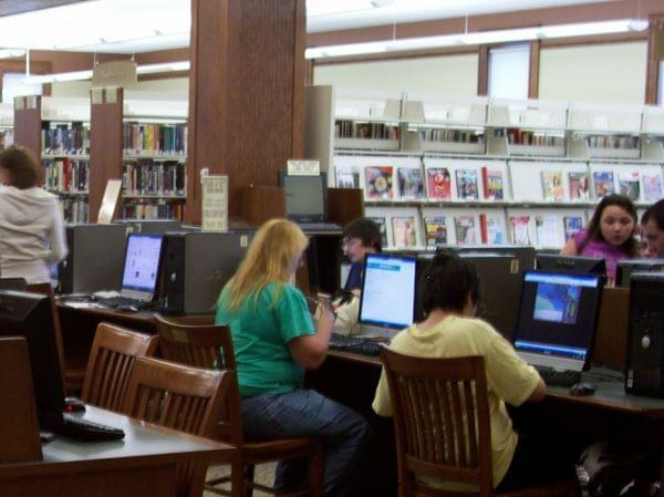 people working at computers in a library