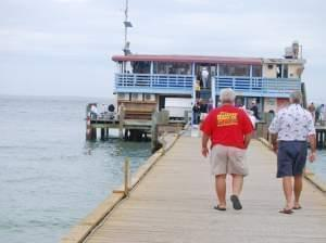 Two men walking on a pier toward a restaurant