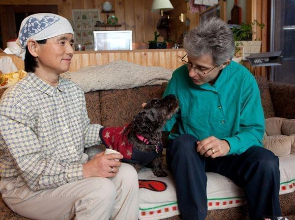 Frances Herbert, right, and her wife, Takako Ueda, pose for photos with their dog, Little Bear, at their home in Dummerston, Vt., Wednesday, Dec. 21, 2011.