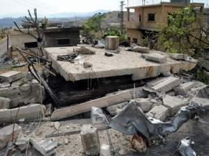 In this photo released by the Syrian official news agency SANA, damaged buildings wrecked by an Israeli airstrike are seen in Damascus, Syria, Sunday, May 5, 2013.