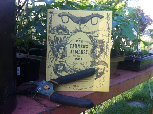 An almanac on a table surrounded by starter plants
