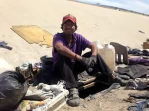 immigrant deported from Riverside, Calif. sits next the hole he lives in beneath Tijuana's fetid river canal.