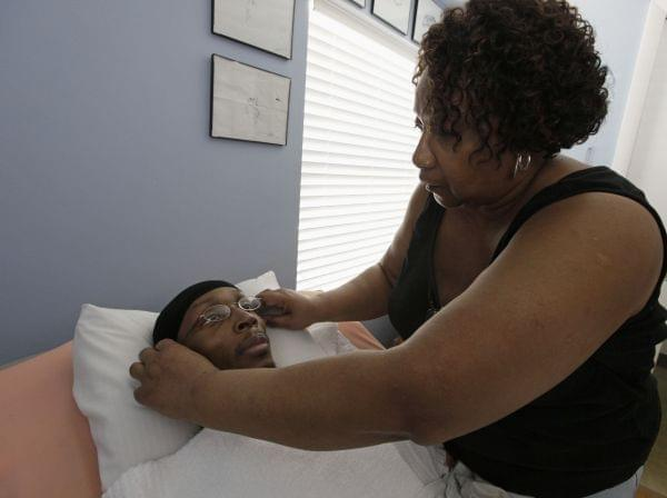In this photo taken April 5, 2011, Annette Clark places glasses on her paralyzed son, Rocky Clark, in the bedroom at their home in Robbins, Ill.