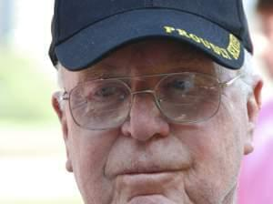 Close up of the face of a world war two veteran. He has a retrospective look, and is wear a world war two hat.