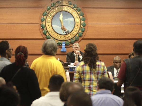 Chicago Board of Education President David Vitale, center, listens to opponents of proposed school closures at a packed board meeting Wednesday, May 22, 2013, in Chicago.