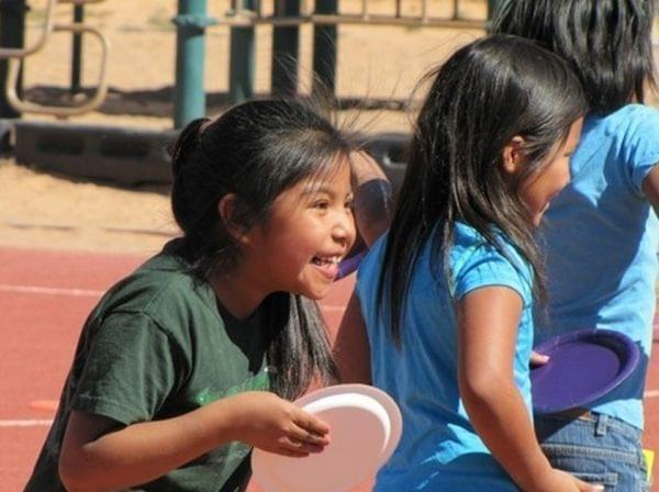 An elementary school student enjoys Field Day on a playground.