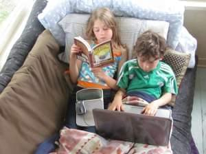 one child reads while another looks at a computer screen