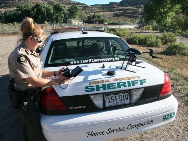 This undated photo provided by the Mesa County, Colo., Sheriff's Department, Deputy Amanda Hill of the Mesa County Sheriff's Office in Colorado prepares to use a Draganflyer X6 drone equipped with a video camera to help search for a suspec