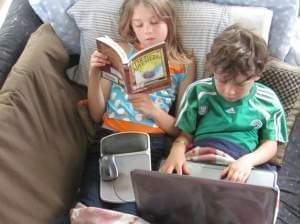 Girl reading and boy using laptop computer