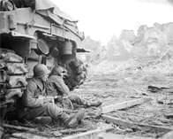 Soldier sitting by a tank