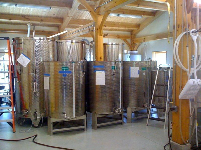 Large vats filled with vine in a vineyard warehouse