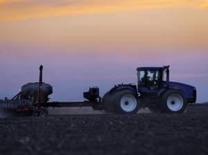 A central Illinois farmer plants corn seed into the evening in Farmingdale, Ill.
