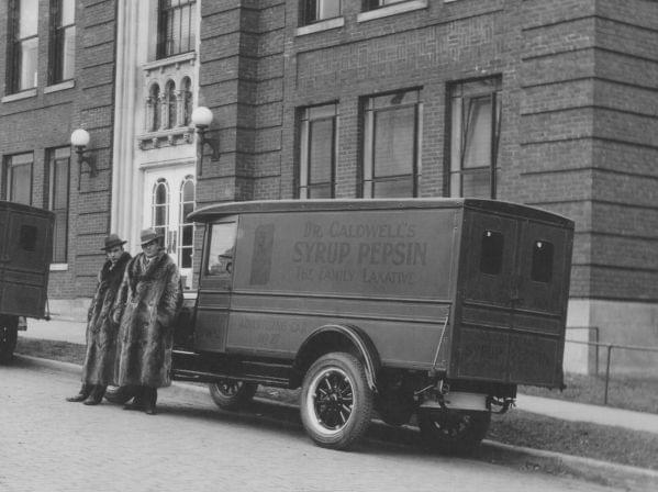 Two men stand in front of the Pepin Syrup Company in the 1920's.