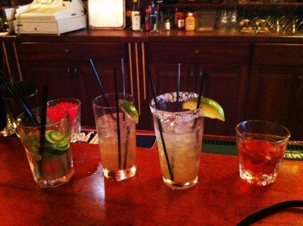 Several cocktails lined up on a bar.